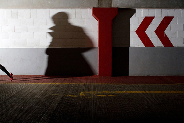 Woman's high-heeled foot exiting the far left of frame and casting a threatening shadow on the wall behind her in a multi storey car park