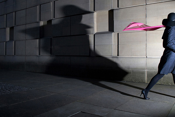 Woman in heels exiting the right of frame wearing a pink scarf and casting a distorted shadow on the wall behind her
